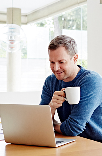 Image of a man drinking coffee while working